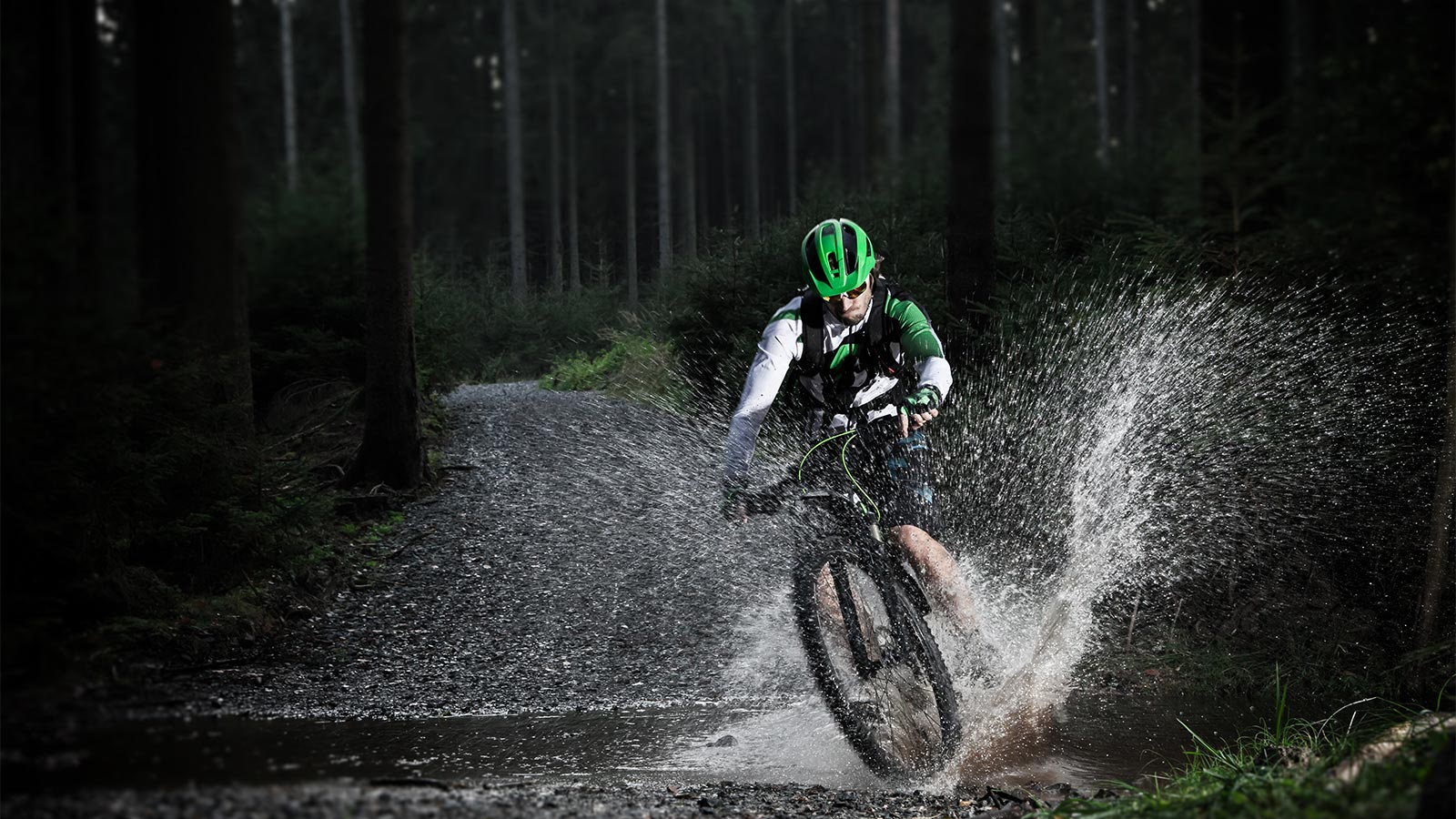 A cyclist passes over a stream with his mtb